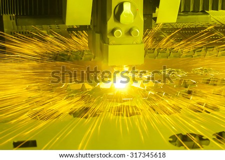 Industrial laser cutting machine with sparks - stock photo