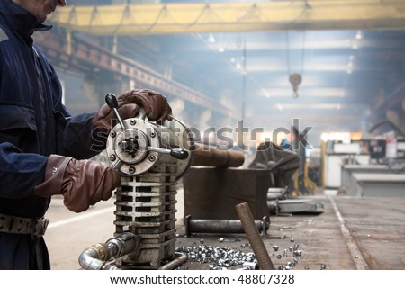 industrial machine for making holes in steel pipes - stock photo