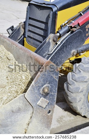 Industrial machinery at  building site. Detail Backhoe bucket with sand. - stock photo