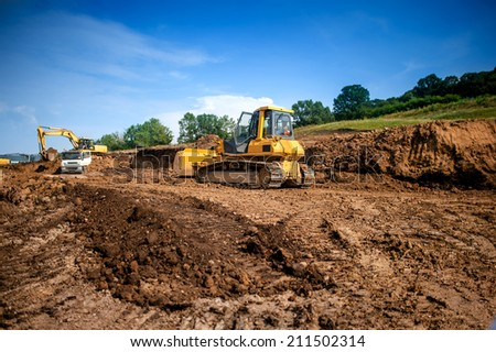 industrial machinery at working construction building site. Excavator, dumper truck and bulldozer working on ground - stock photo