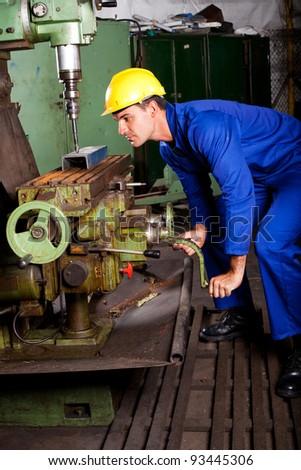 industrial machinist operating machine tool - stock photo
