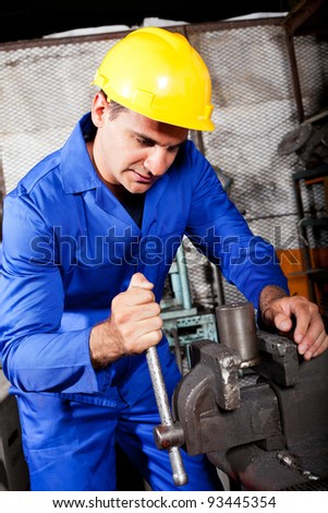 industrial machinist working on vice grip in workshop - stock photo
