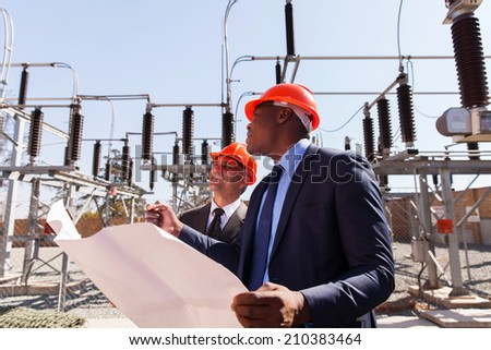 industrial managers working in electric substation - stock photo