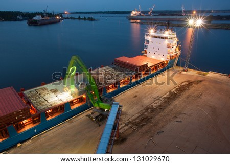Industrial night at port - crane is loading ship for transportation - stock photo