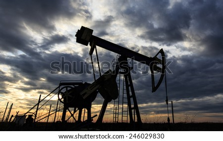 Industrial oil and gas well contour, profiled on storm clouds at sunset - stock photo
