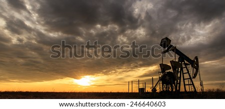 Industrial oil and gas well pump at sunset