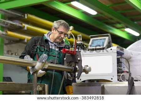 Industrial operator setting  computer controlled process of orbital welding machine in inox pipes manufacturing workshop. - stock photo