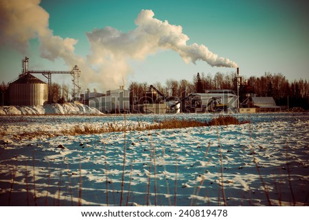 industrial park with chimney and white smoke on blue sky - retro vintage look - stock photo