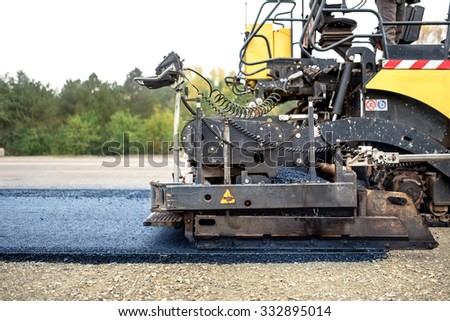 industrial pavement truck laying fresh asphalt on construction site, asphalting  - stock photo