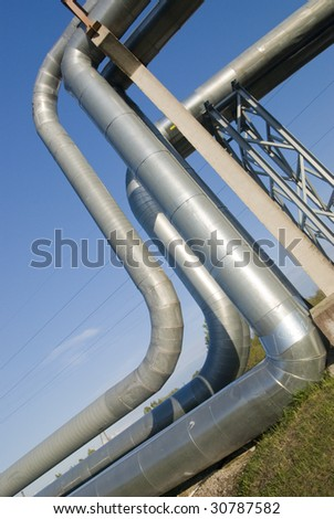 industrial pipelines on pipe-bridge against blue sky.