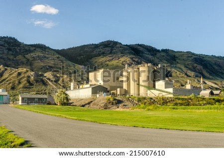 Industrial Plant at the foot of a Hill at Sunset - stock photo