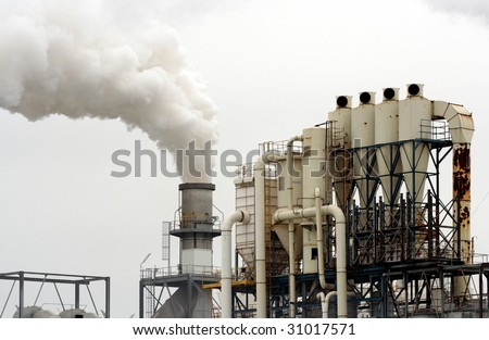 Industrial plant exhausting white smoke into the atmosphere.