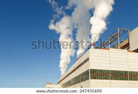 Industrial plant of a furniture factory with smoking chimneys - stock photo