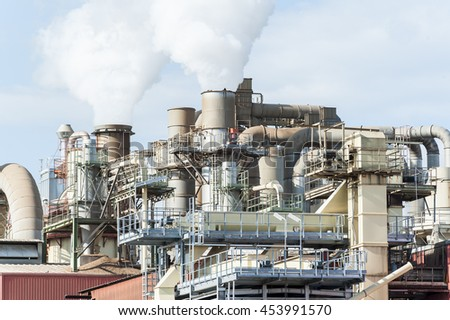 Industrial plant of a furniture factory with smoking smokestack,tube,silos. - stock photo