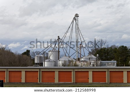 Industrial plant surrounded by water and blue cloudy sky. - stock photo