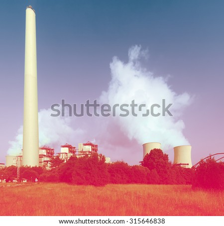 Industrial plant with chimney and cooling towers in sunny day - stock photo