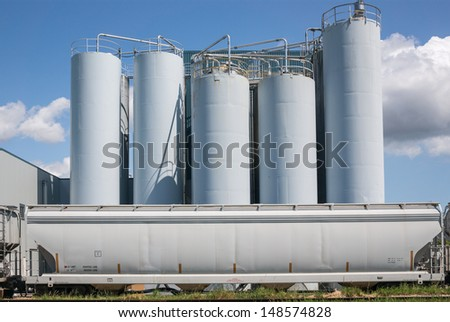 Industrial plant with silos against blue sky - stock photo