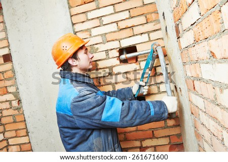 industrial plumber fixing pipe in water heating engineering system of building  - stock photo