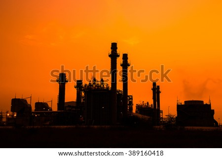 Industrial power plant in silhouette image at sun set.