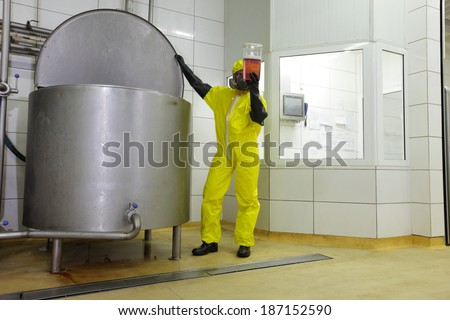 industrial professional , in protective uniform,mask,goggles,gloves and wellies checking sample in plastic container at large industrial tank in plant
