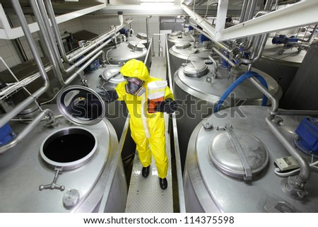 industrial professional with sample in container, in protective uniform,mask,goggle s,gloves and wellies controlling industrial process - stock photo
