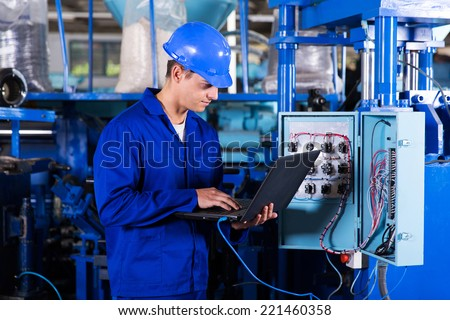 industrial programmer checking control box status with laptop computer - stock photo