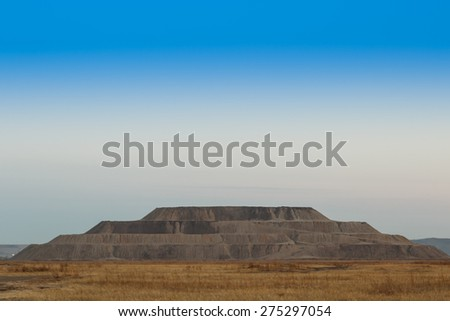 Industrial pyramid of earth extracted in the quarry. Mountain waste rock in the shape a pyramid. - stock photo