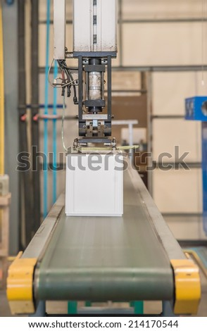 Industrial robot working in plastic factory - stock photo