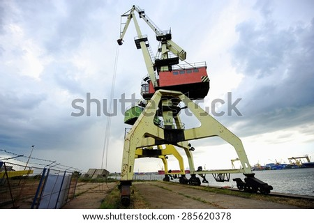 Industrial shipping cranes for containers in a port with dramatic sky on background - stock photo