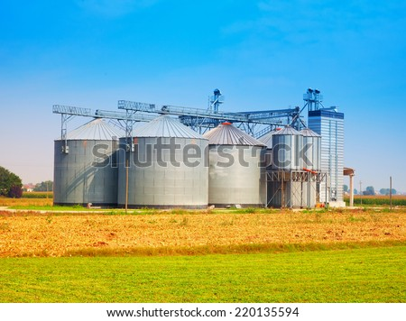 Industrial silos under blue sky, in the fields - stock photo