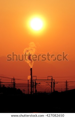 Industrial smoke from a chimney against a foggy orange evening sky and sunset glow.