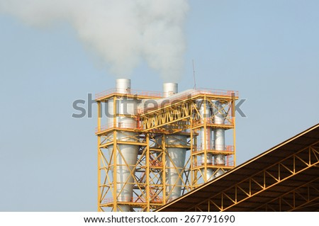 industrial smoke from chimney on blue sky - stock photo