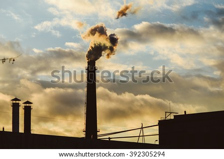 Industrial smoke from chimney on sunset sky - stock photo