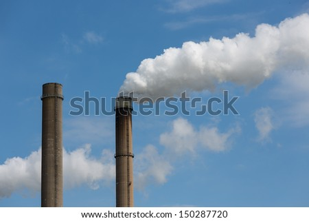 Industrial smoke stacks of a power plant. - stock photo