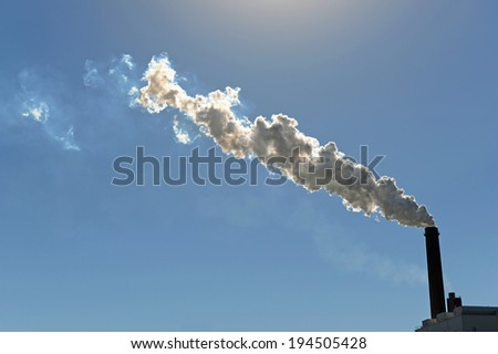 Industrial smokestack billowing smoke into atmosphere - stock photo