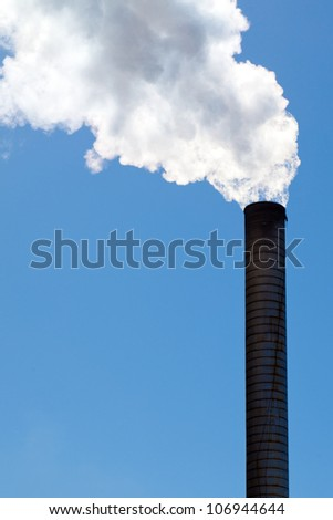 Industrial smokestack emitting clouds of white smoke or steam against blue sky. Copy space.