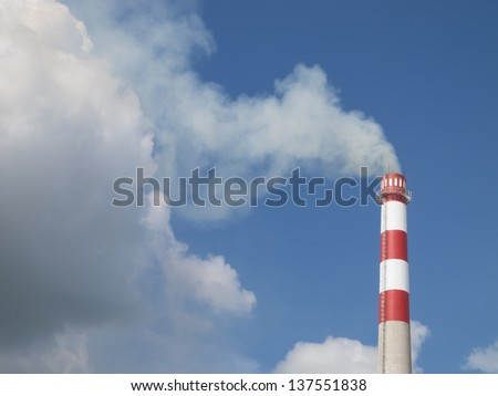 Industrial smokestack on blue sky