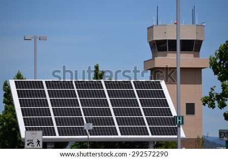 Industrial solar panel with air traffic control tower - stock photo