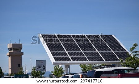 Industrial solar panel with air traffic control tower in background - stock photo
