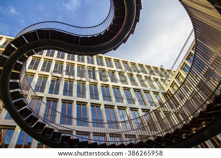 Industrial spiral staircase on orange building background.Helical contemporary steel unusual stairway.Moving up.Stylish outdoor ladder. Winding road across through difficulties to success with company - stock photo