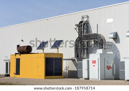 Industrial standby generator and electrical service with solar panels. - stock photo