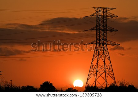 Industrial Sunrise with electrical pylon - stock photo