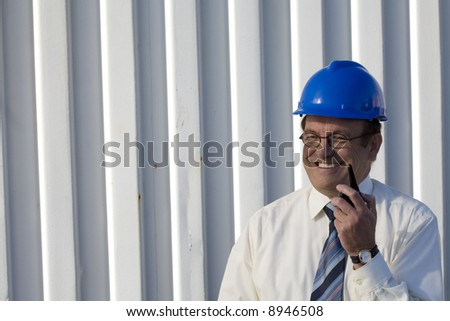 Industrial surveyor on location talking on his radio - stock photo
