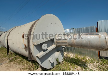 Industrial tank on grass nearby the metal fence