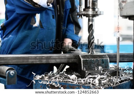 industrial technician working on a drilling machine - making a hole in a metal bar