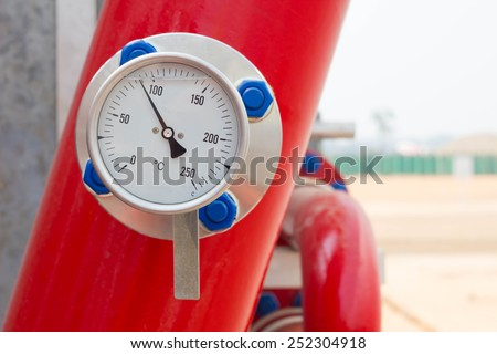 Industrial temperature gauge with out of focus pipes in background