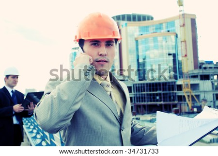 Industrial theme: constructor standing at a site area.