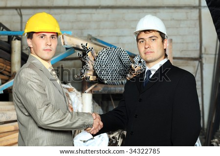 Industrial theme: two businessman shaking their hands at a manufacturing area.