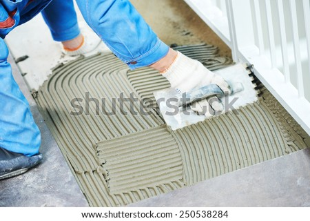 industrial tiler builder worker installing floor tile at repair renovation work - stock photo