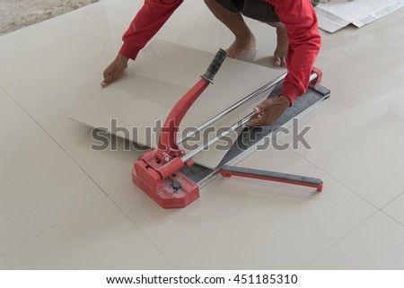 Industrial tiler builder worker working with floor tile cutting equipment at repair renovation work,Worker working on laying of porcelain tiles - stock photo